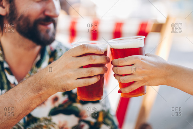 Close up detail of couple cheering with beer during a summer day picnic outdoors