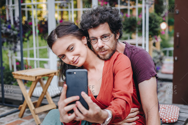 Authentic image of beautiful young couple in love taking selfie on smartphone during summer music festival