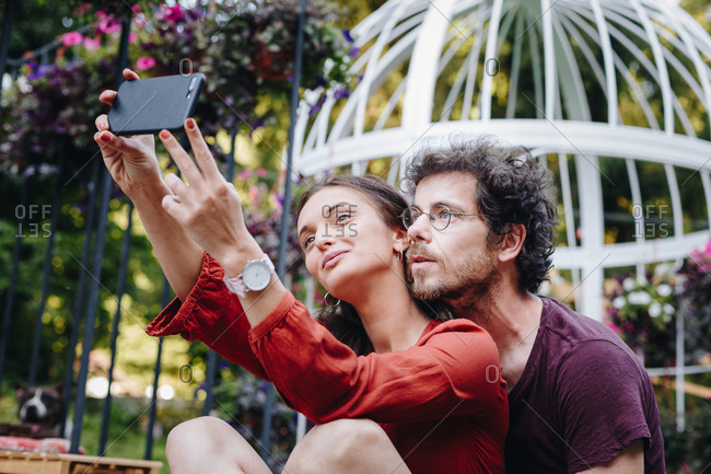 Beautiful young couple in love taking selfie with smartphone outdoors during summer