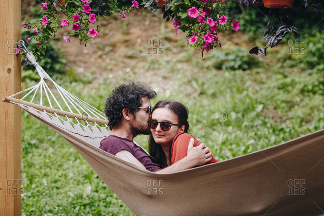 Young couple in love sharing a kiss outdoors in summer while resting in a hammock outdoors