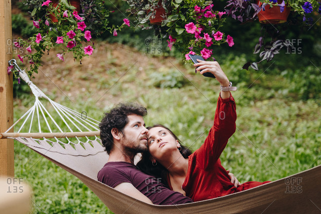 Beautiful young couple in love taking selfie with smartphone while resting on a hammock