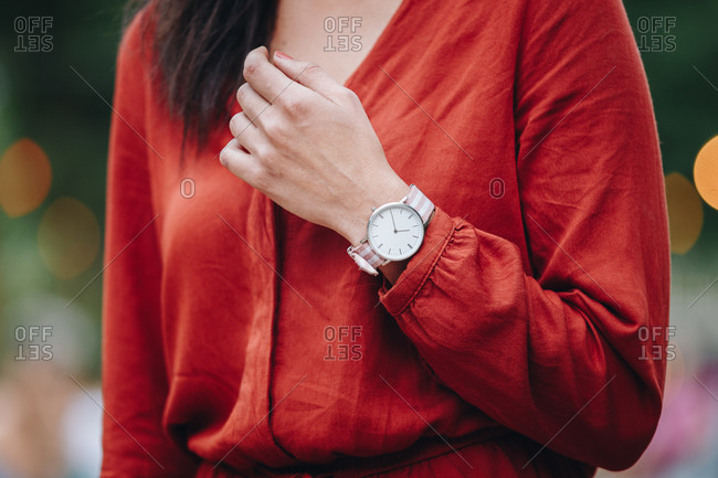 Street style fashion details. Close up, young fashion blogger wearing white and pink analog wrist watch.