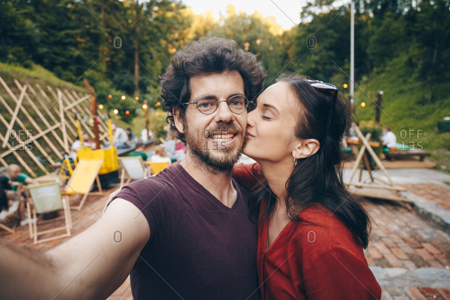 Beautiful young couple in love taking selfie on smartphone during summer music festival