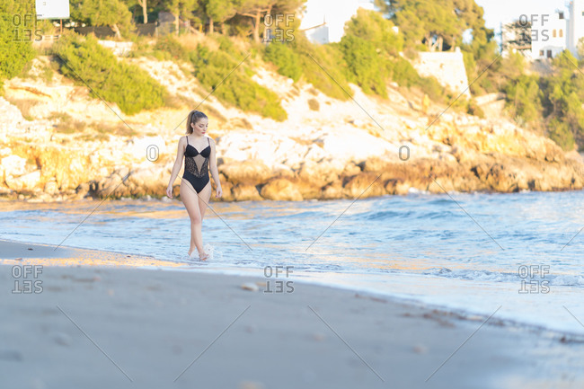 Young blonde woman with blue eyes, dressed in a black swimsuit, walking happily on the beach