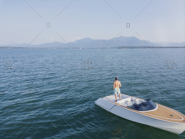 Germany- Bavaria- Shirtless man standing on motorboat floating in Chiemsee lake admiring view of distant Chiemgau Alps