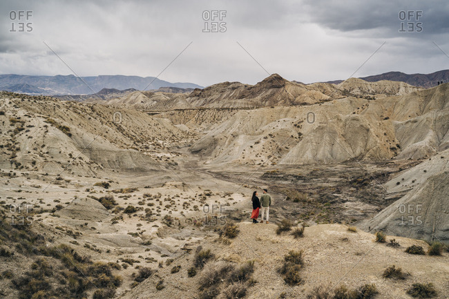 Young couple in desert landscape under cloudy sky- Almeria- Andalusia- Spain