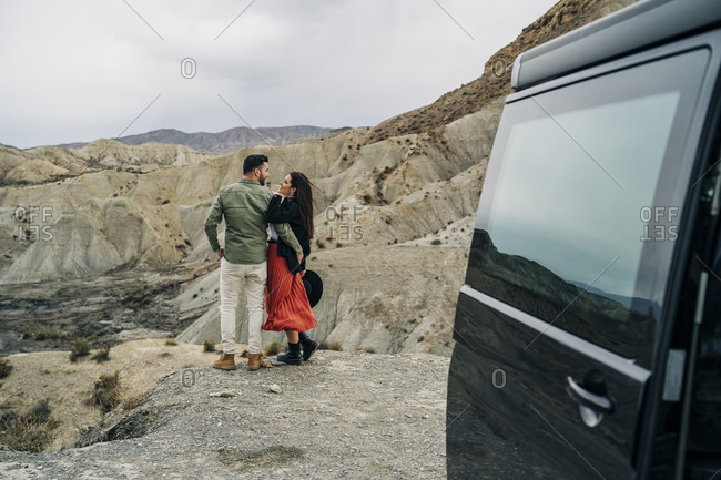 Young couple in desert landscape under cloudy sky next to camper van- Almeria- Andalusia- Spain