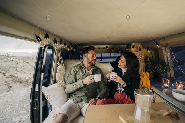 Happy young couple inside camper van