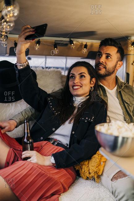 Happy young couple taking a selfie inside camper van