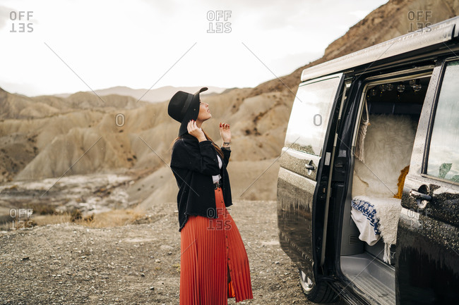 Young woman in desert landscape standing next to camper van- Almeria- Andalusia- Spain