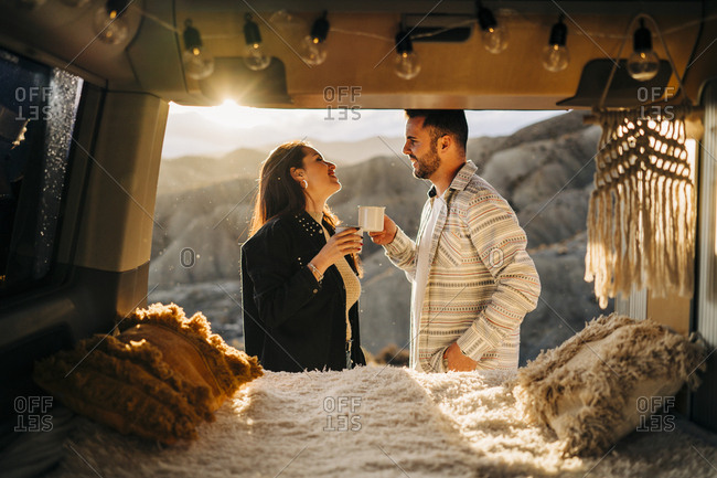 Young couple on a trip with camper van at sunset- Almeria- Andalusia- Spain