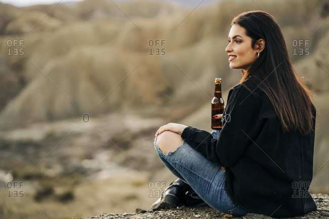Young woman sitting in desert landscape drinking a beer- Almeria- Andalusia- Spain