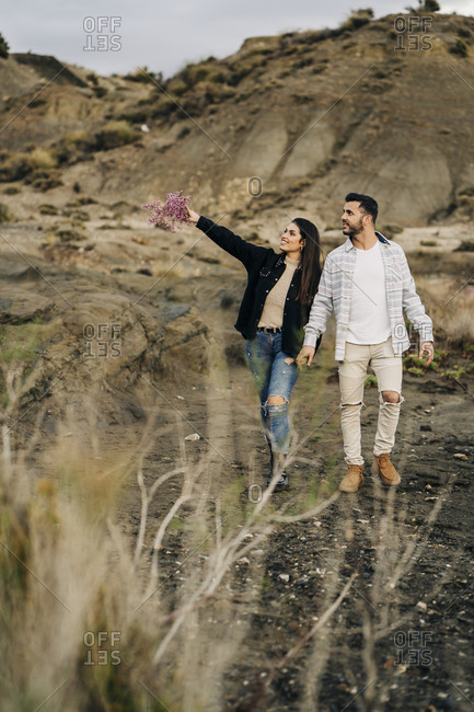 Young couple walking hand in hand through desert landscape- Almeria- Andalusia- Spain