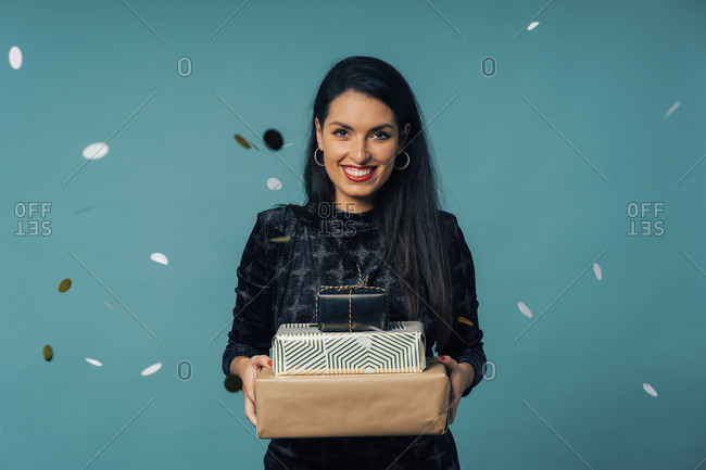 Portrait of young woman dressed for a party- celebrating Christmas with gifts and champagne