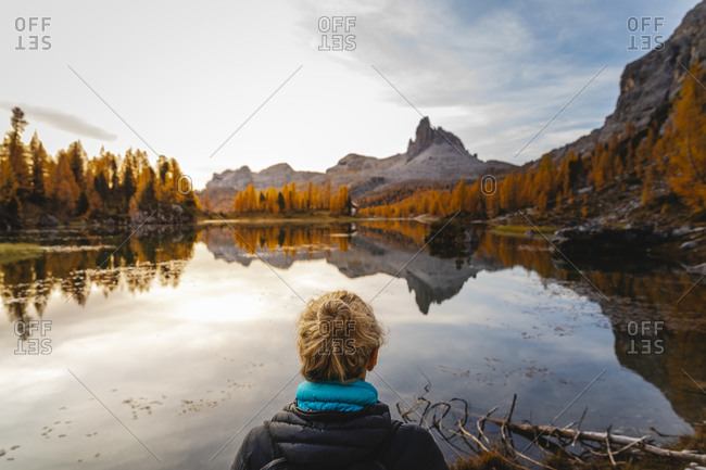 Female hiker looking at the mountain landscape with lake at the first light of the day- Dolomites Alps- Cortina- Italy
