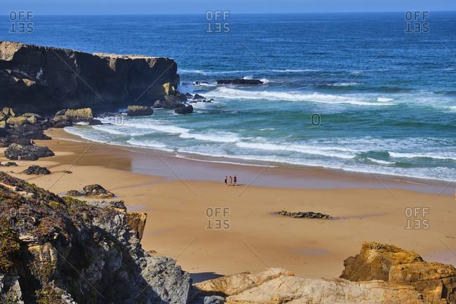 Portugal- Alentejo- Vila Nova de Milfontes- Three people walking along Malhao beach in summer