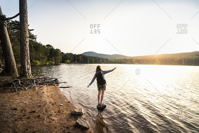 Rear view of female hiker taking a step- Reservoir de L'Ospedale in the morning- Corse-du-Sud- Corsica- France