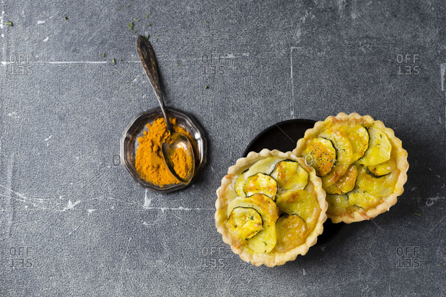 Directly above shot of vegetable tartlets with turmeric served on table