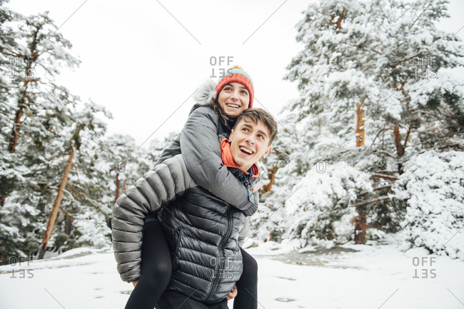 Portrait of happy young man giving his girlfriend a piggyback ride in winter forest
