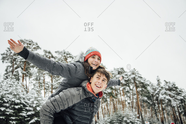 Portrait of smiling young man giving his happy girlfriend a piggyback ride in winter forest