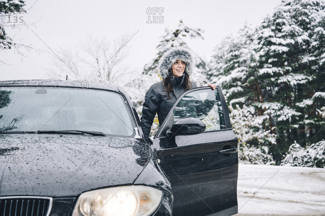 Smiling young woman standing beside parked car in winter forest looking at distance