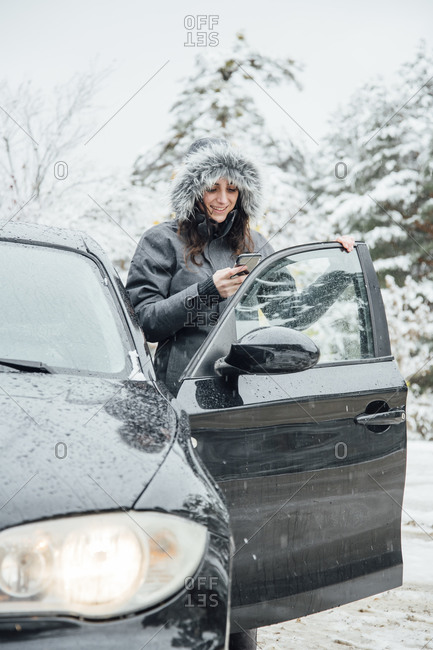 Smiling young woman standing beside parked car in winter forest looking at cell phone