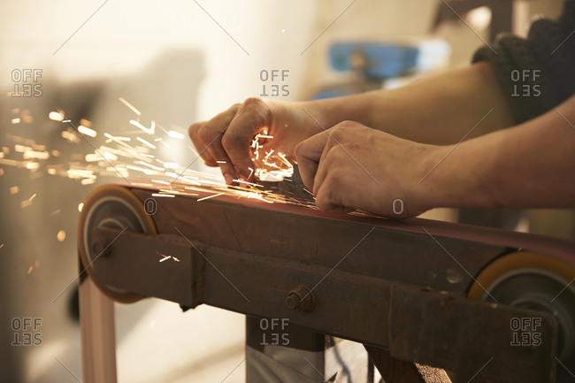 Man grinding a blade in a workshop