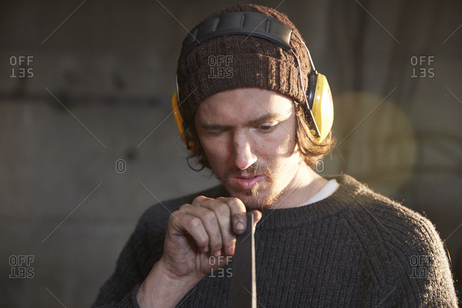 Man checking self-made knife in a workshop