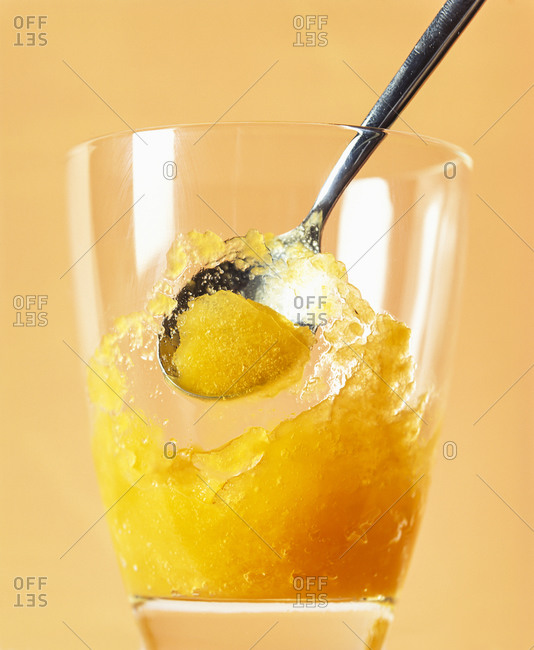 Mango fruit ice cream sorbet in drinking glass against orange background