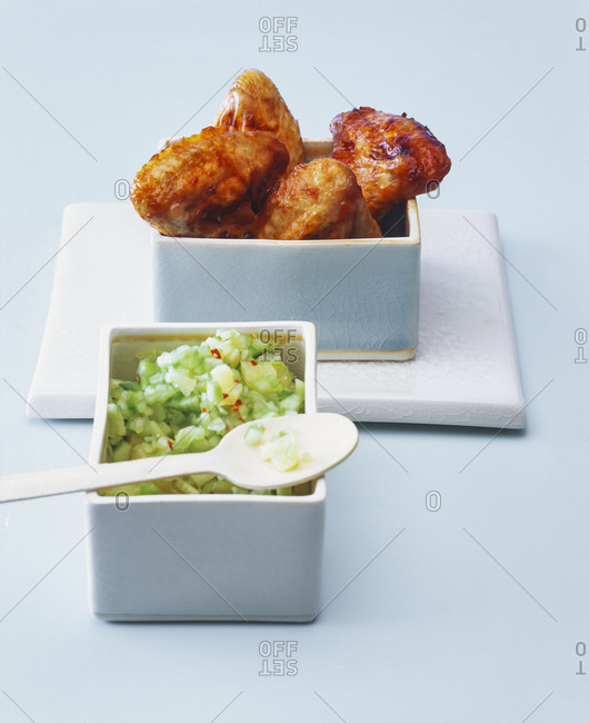 Roasted chicken wings with cucumber pineapple salsa on blue background