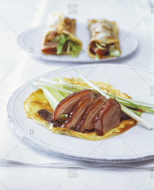 Close-up of roasted goose breast with pancakes and scallions served in plates on table