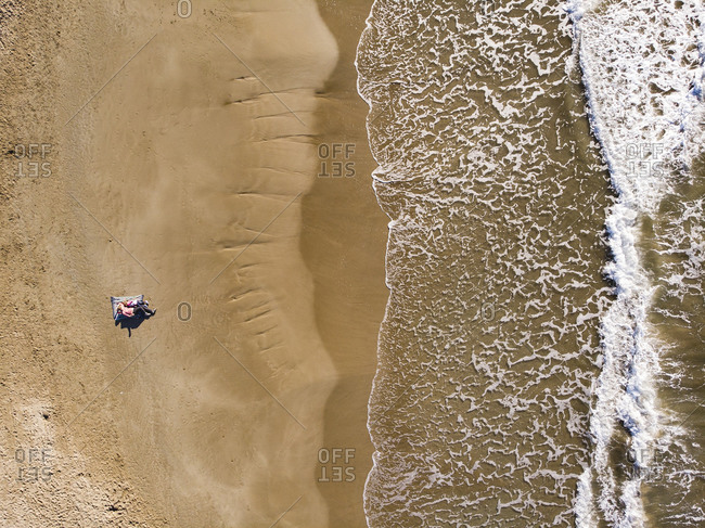 Spain- Sitges- aerial view of mother and daughter lying on sandy beach