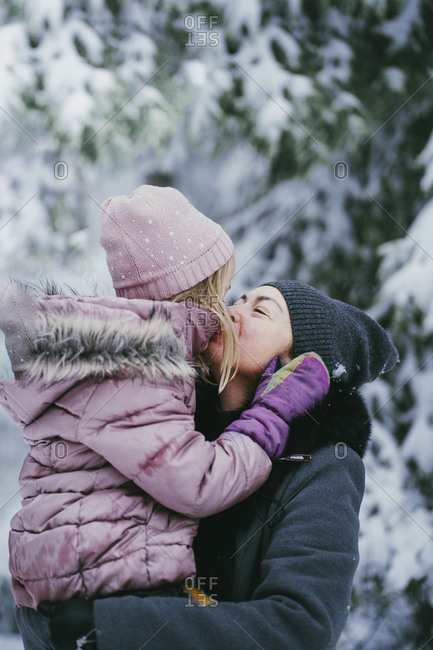 Mother kissing her little daughter in winter forest