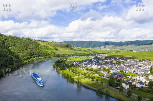 Drone shot of cruise ship on Mosel River by town against cloudy sky- Germany