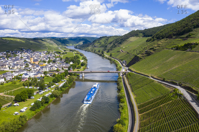 Drone shot of passenger ship on Mosel River by town against cloudy sky- Germany