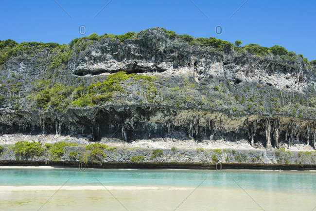 Beach against The grey Lekiny cliffs- Ouvea- Loyalty Islands- New Caledonia