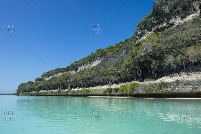 The grey Lekiny cliffs by turquoise sea against clear sky- Ouvea- Loyalty Islands- New Caledonia