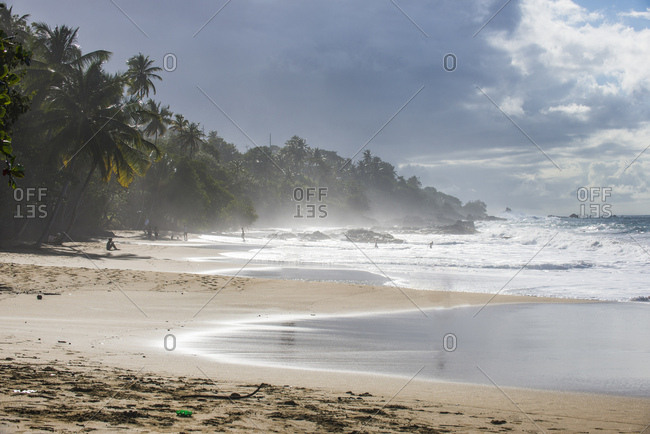Scenic view of waves splashing at shore against cloudy sky at Trinidad and Tobago- Caribbean