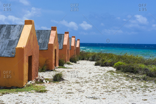 Slave huts at beach against blue sky during sunny day- Bonaire- ABC Islands- Caribbean Netherlands