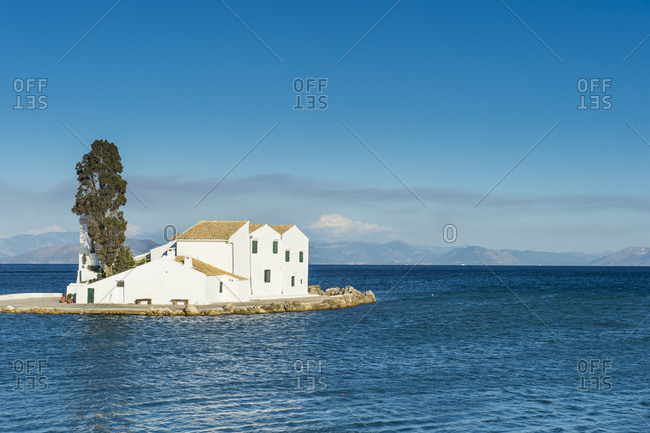 Vlacherna Monastery amidst sea against blue sky at Kanoni- Ionian Islands- Greece