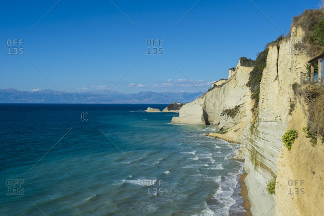 Scenic view of cliff by sea at Loggas beach against blue sky- Corfu- Ionian islands- Greece