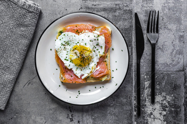 Directly above shot of toasted bread with salmon and heart shaped fried egg in plate on table