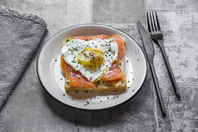 High angle view of toasted bread with salmon and heart shaped fried egg in plate on table