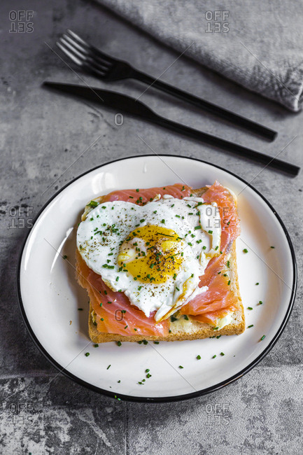 Close-up of toasted bread with salmon and heart shaped fried egg in plate on table