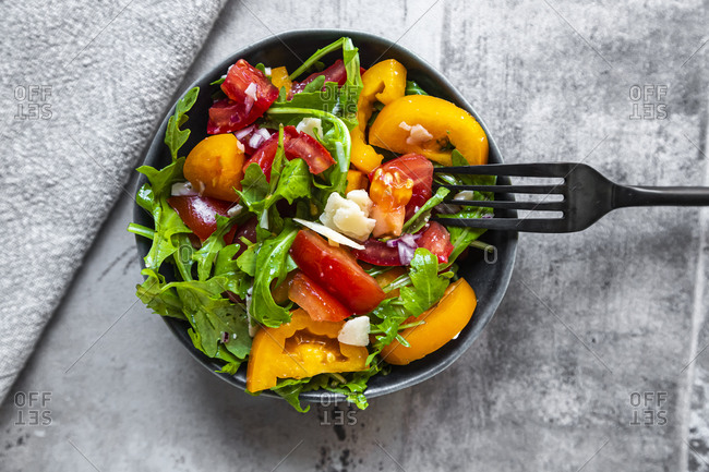 Bowl of salad with red and yellow tomatoes- arugula and Parmesan
