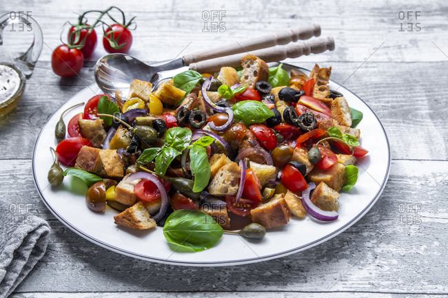 Panzanella- Italian bread salad with roasted ciabatta- tomatoes- olives- red onion- caper apples and basil on plate