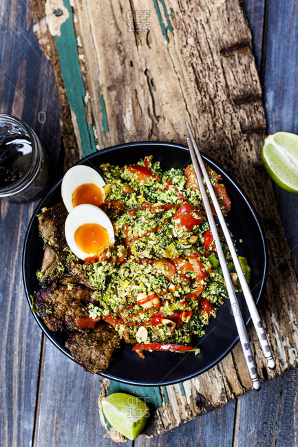 Thai style fried broccoli rice (shredded broccoli) with beef slices- eggs- and spicy sauce (ketogenic diet- paleo diet- low carb)