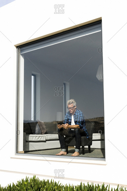Casual businessman sitting in modern home looking at tablet