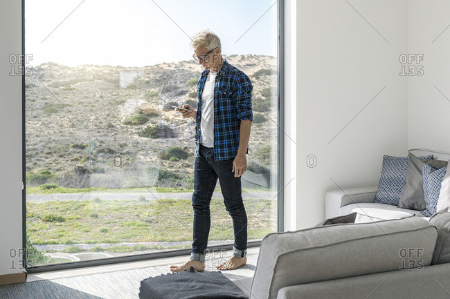 Casual businessman in front of window in modern home holding smartphone