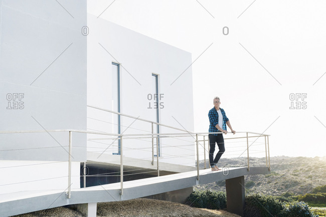 Casual man standing in front of his modern home looking at the landscape